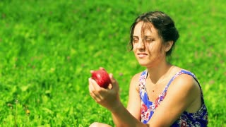 Happy woman sitting on the meadow and playing with apple