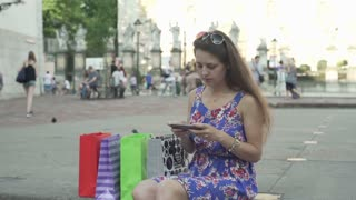 Happy woman sitting on the square and texting, steadycam shot
