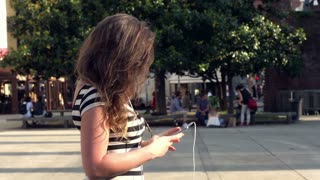Happy woman standing on the square and texting on smartphone, steadycam shot