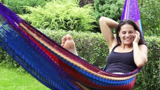 Happy woman talking on the phone in a hammock, slow motion shot at 240fps