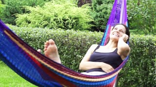 Happy woman talking on the phone in a hammock, slow motion shot at 60fps