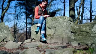 happy woman typing on her laptop and sitting on the rock in the mountainous area