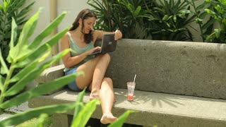 Happy woman using laptop in the garden and sitting on bench