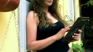 Happy woman using tablet on the balcony, steadycam shot