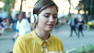Happy woman wearing headphones and watching something on tablet