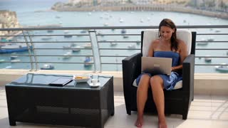Happy woman with laptop computer on the terrace