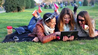Happy women lying on blanket in park watch tablet and eat apple, steadycam shot.