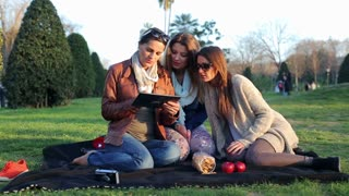 Happy women sit in park on blanket usin tablet, steadycam shot.