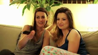 Happy women sitting on sofa in pyjamas and watching tv.