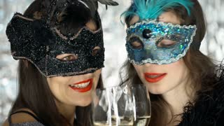 Happy women wearing carnival masks and drinking champagne, steadycam shot