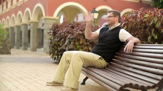 Happy young couple in tourist resort sitting on the bench, steadicam shot