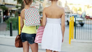 Happy young female friends walking with shopping bags in the city, slow motion