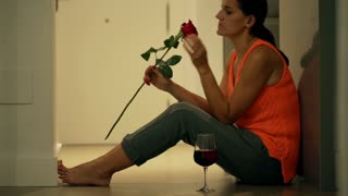 Heartbroken woman sitting on the floor with red rose and drinking wine