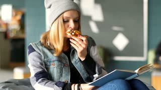 Hipster girl reading book in the restaurant and eating slice of pizza