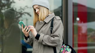 Hipster girl smiling while typing message on smartphone
