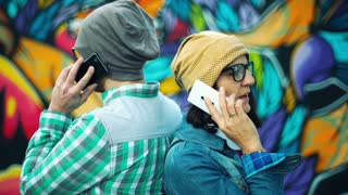 Hipsters leaning on each other and chatting on cellphones