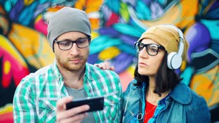 Hipsters listening music on headphones and smiling to the camera