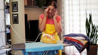 housekeeper ironing and chatting on the phone