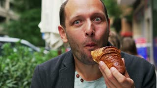 Hungry man eating croissant and looking funny in the street cafe