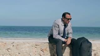 Irritated businessman sitting on the wall, steadycam shot