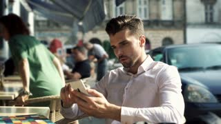 Irritated man looking on smartphone and waiting for someone