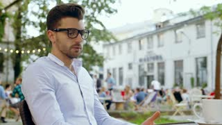 Irritated man waiting for someone and checking time on smartphone