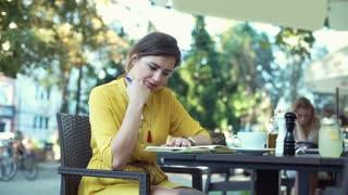 Irritated woman checking time while writing something in her notebook