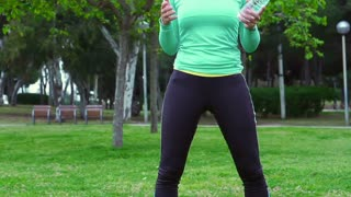 Jogger standing in the park and throwing bottle, steadycam shot, slow motion sho