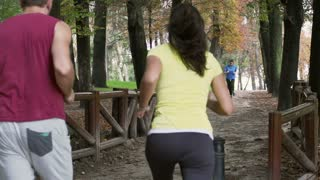 Joggers passing each other on the path, slow motion shot at 240fps, steadycam