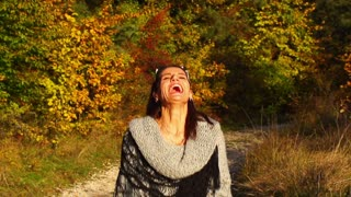 Joyful woman playing with leaves in the autumnal scenery, steadycam shot, slow m