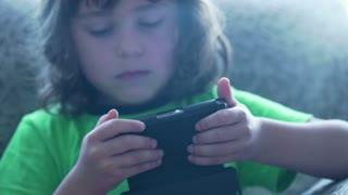 Little boy playing game on smartphone and looking occupied, steadycam shot