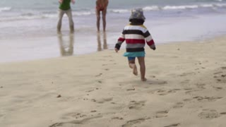 Little boy running to parents on the beach, slow motion shot at 240fps