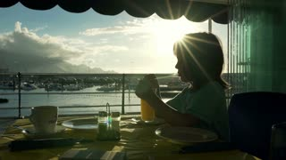 Little boy sitting in the restaurant on seashore and drinking juice, steadycam s