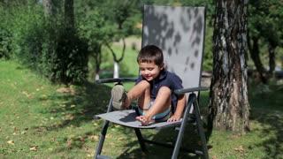 little boy sitting under the tree in the garden