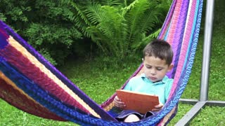 Little boy using tablet in a hammock, slow motion shot at 240fps