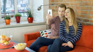 Lovely couple doing photo on the smartphone while sitting on the sofa, steadycam