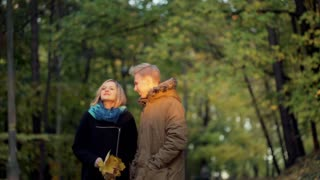 Lovely couple walking in the autumnal park and chatting with each other