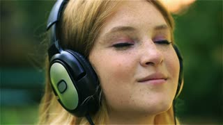 Lovely girl listening music and sending kiss to the camera, steadycam shot
