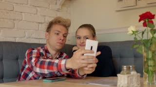 Loving couple doing selfies on smartphone in the cafe