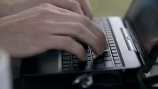 Male hands touch buttons on keybaord while typing something, steadycam shot