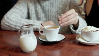 Man adding sugar to his coffee and mixing it in the restaurant