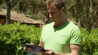 Man browsing internet on tablet while standing in the bushes, steadycam shot