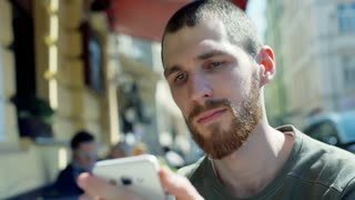 Man browsing internet while sitting in outdoor cafe and smiling to the camera