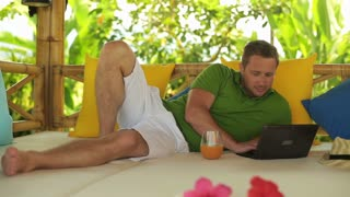 Man chatting on tablet and lying on bed