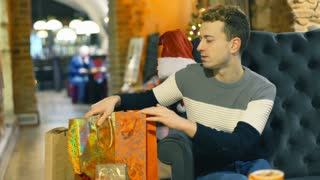 Man checking presents while sitting in the cafe and smiling to the camera, stead