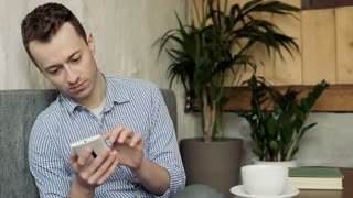 Man checks his smartphone in the cafe and receives bad news