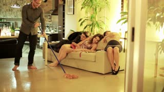 man cleaning floor after the party and looking at girls lying on the sofa