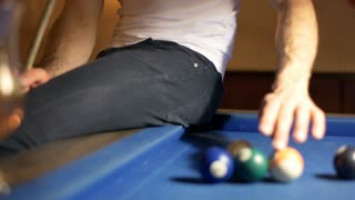 Man collects balls while sitting on billiard's table and smiling to the camera,