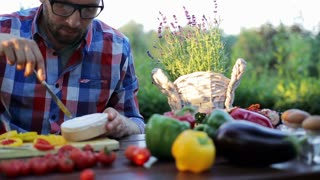 man cutting blue cheese and sitting by the table in the garden