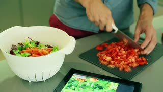 Man cutting tomato and throwing it to the bowl with salad, steadycam shot